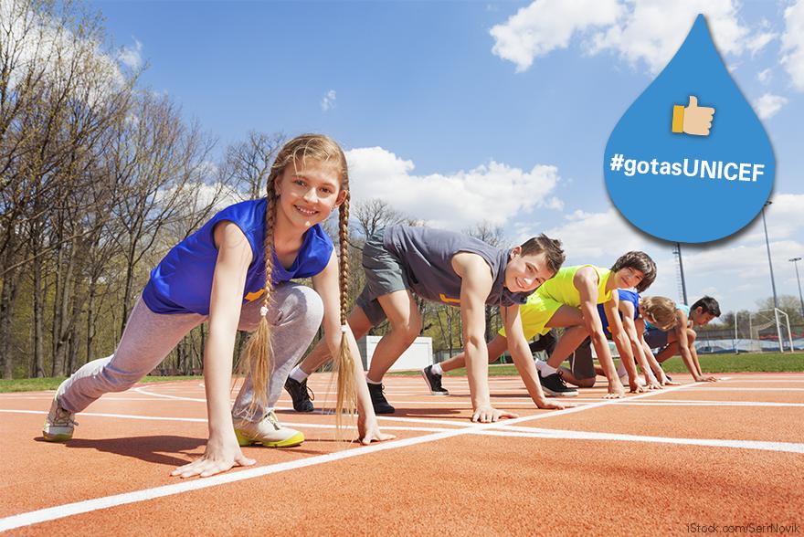 Unas niñas y niños esperan en posición de salida a que comience una carrera en una pista de atletismo.